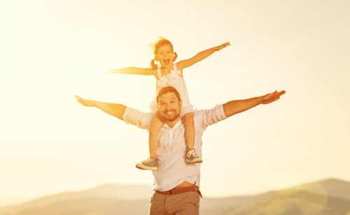 father's day. child daughter sits on her dad shoulders outdoors on a summer beach